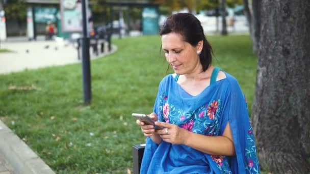 Portrait of Amazing Woman with Smartphone Outdoors. Pretty Brunette Using Her Mobile Phone with Touch Screen Standing in the Park