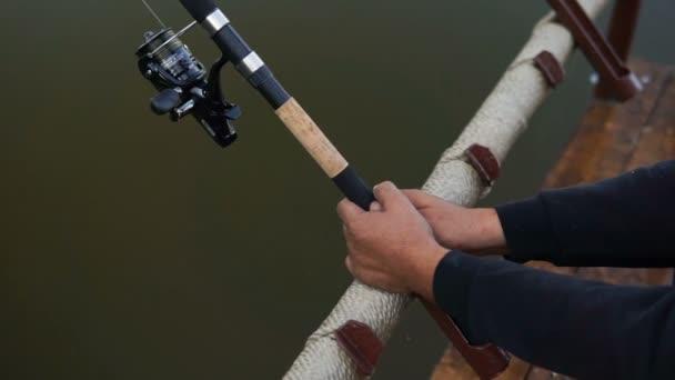 A halász és a horgászbot. Egy kéz, gazdaság egy forgó rúd és tekercs csavaró részlete.