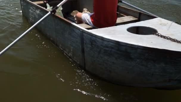 Dva lidé na lodi plovoucí na řece