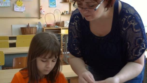 A teacher and four children. the teacher teaches students to model plasticine