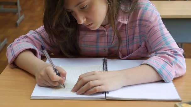 Boldog általános iskolás gyerekek rajz osztályban közös asztalnál.