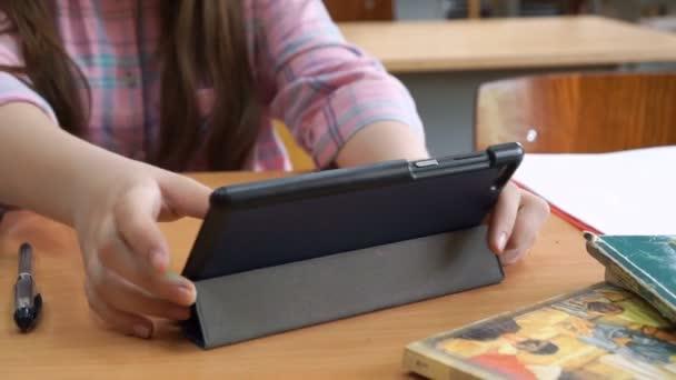 Diák lány iskolai tanteremben tanul tabletta