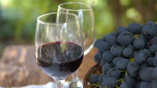 Stillleben mit Korb mit Trauben und einem Glas Wein. Herbstfrüchte, Steadicam-Schuss.
