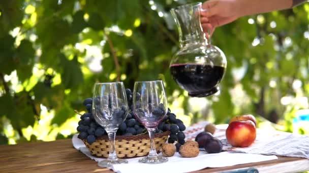 Muž červené víno nalijte do sklenic. Zátiší s košíkem s hrozny a víno. Podzimní ovoce, Steadicam zastřelil