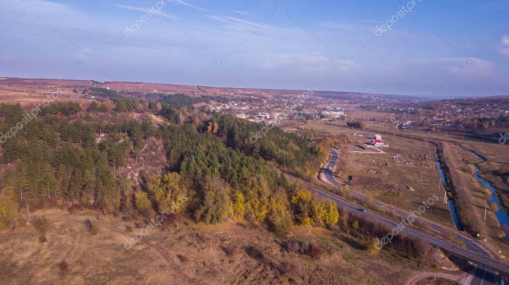 Aerial view of highway crossing villages and forest hills in Moldova.