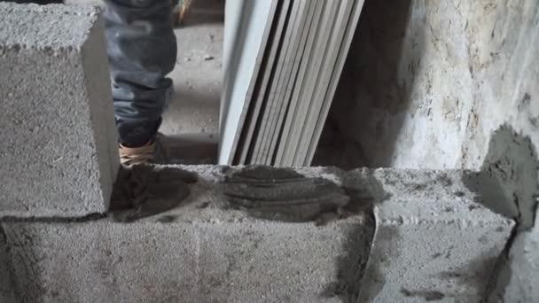 Stavební dělník staví zdi, detailní pohled na staveništi