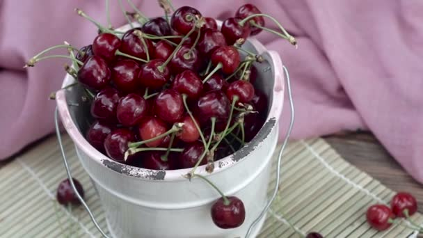 Cherries in a white bowl on a wooden table.