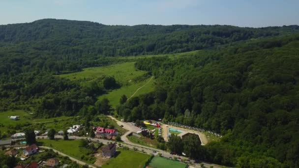 Drone flies over the green forest and small city in mountainous area sunny day in summer season. Carpatians mountains, Romania.