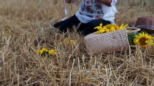 Nők fonják koszorú napraforgó és búza a réten.