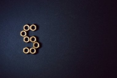 Golden mechanic nuts forming shapes and numbers in dark background