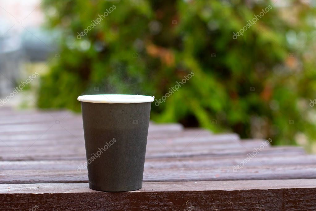Gray plastic cup with coffee on the background of branches in park