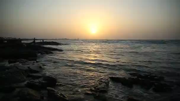 Nádherný západ slunce na pláži, úžasné barvy, světelný paprsek zářící v mračně. Ázerbájdžánské moře a pláž. Blíží se zvuk mořských vln. Rybář loví v moři. Tá
