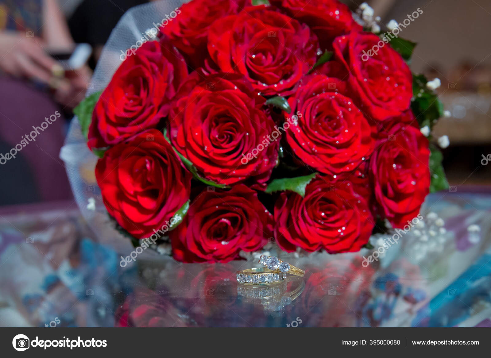 Glass Table Wedding Rings Next To A Red Flower Bouquet Selective Focuse Bride And Groom With Engagement Gold Rings Put On The Table And Next To Them Lies A Wedding