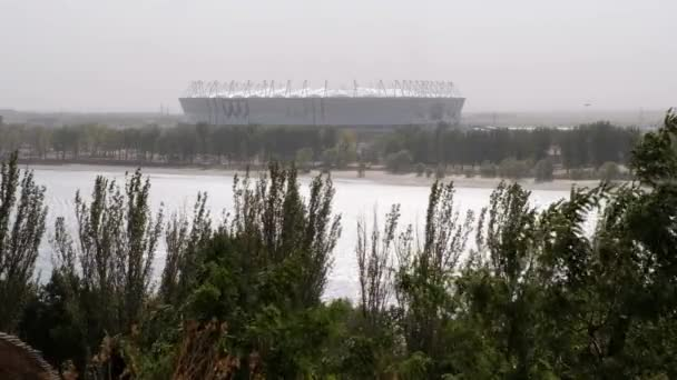 view of the river Don through the trees in windy weather amidst a large structure, Rostov-on-Don, Russia withdrawn 09-23-2017