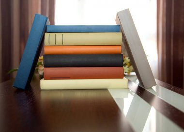 colorful book tower on  wooden table with space to write