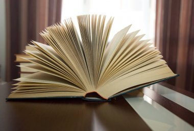 thick open book in fan on wooden table against backlight