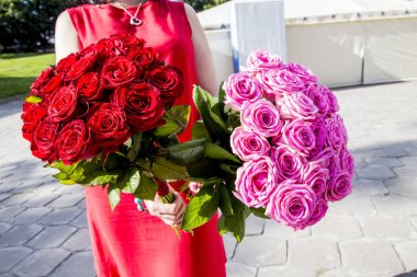 woman floristry red dress holds in her hands 2 bouquet of red and pink roses on a sunny day
