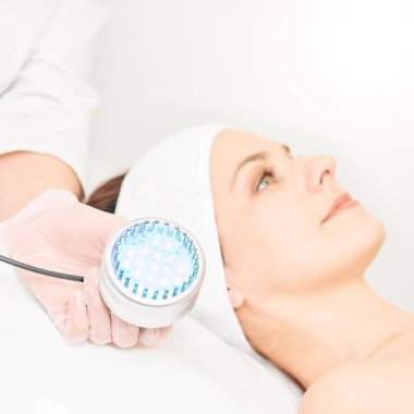 Skincare cosmetology facial procedure. Beauty woman face. Blue light medical therapy. Specialist hand