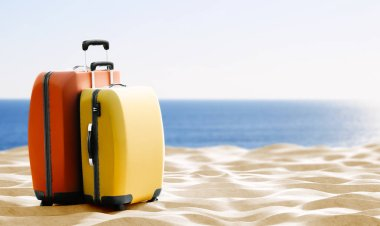 travel theme background with colorful luggage on sand