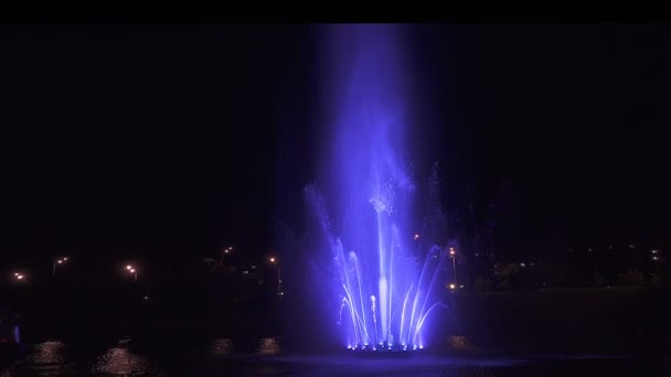 Colorful dancing fountain at night on dark background.