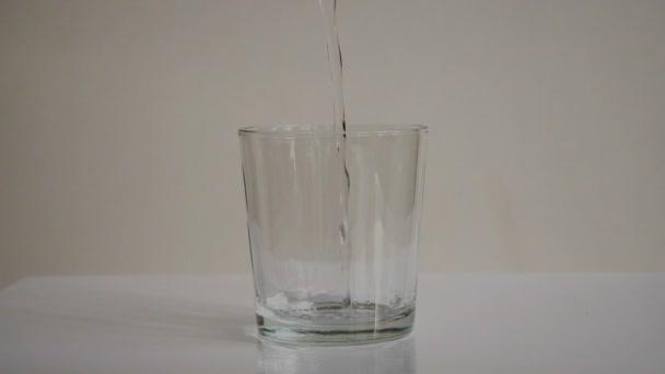 Chiara acqua versando nel bicchiere trasparente