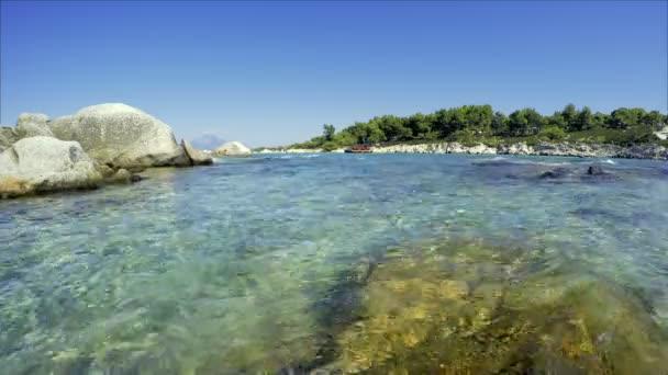 Modrá obloha nad zálivem s Crystal tyrkysová voda a borový les. Letní moře pobřeží krajiny Chalkidiki Sithonia, Řecko