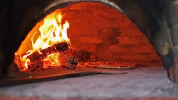 Pizza pečení v planoucí horké dřevo padáka trouba. Kuchaři připravující pizzu v komerční kuchyni. Pizzerii. Příprava jídla.