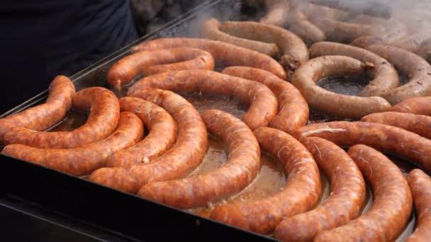 Pouliční prodejce vaření hovězí a vepřové klobásy na stánek s jídlem. Chutné klobásy na velkých komerčních plotna varná deska.