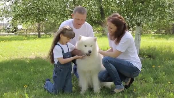 Eine dreiköpfige Familie geht mit einem großen Hund im Park spazieren. Rund um den blühenden Apfelbaum füttern Eltern mit ihrer Tochter ihren Hund.