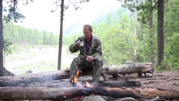 A man drinks alcohol in a forest by the fire. The tourist drank strong alcohol and poured it into the fire from the mug.