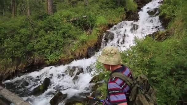 Turistické procházky podél protokolu přes řeku. Mužské cestovatel prochází horského potoka na úzké desky
