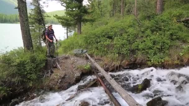 Turistické-překřížené protokol přes řeku. Cestovatel člověk stojí u stromu a rychlé horské bystřiny