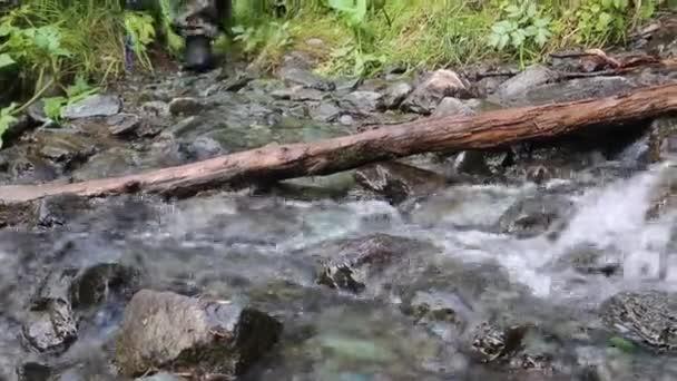 Nohy muže v botách chodit přes kameny ve vodě. Muž ve vojenské boty přes Brod řeky