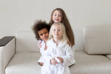 Children of the planet Earth of different nationalities. Three beautiful little girls in white coats after a shower together blonde, black and brown-haired. stock vector