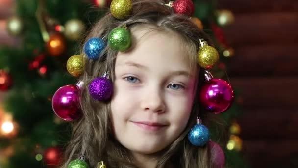 Mädchen mit Weihnachtsschmuck in ihrem hair.little schönes Mädchen geflochten Weihnachtsbaumschmuck in ihrem Haar.