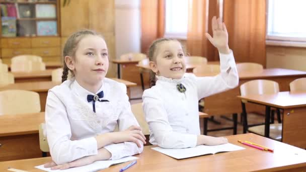 Schoolgirl raises her hand to answer the teachers question.Two girls of a teenager schoolgirl are sitting at the table, one student raises her hand to answer the teachers question the second girl knows the subject of the lesson lesson