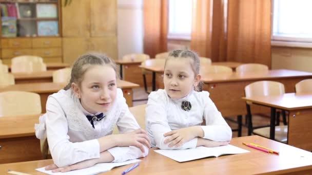 Schoolgirl felemeli a kezét, hogy válaszoljon a tanár kérdésére. Két lány egy tinédzser iskolás ül az asztalnál, egy diák emeli a kezét, hogy válaszoljon a tanár kérdésére, a második lány tudja, a tárgya a leckét lecke