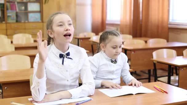 Školka zvedne ruku, aby odpověděla na učitelovu otázku. dvě dívky z puberťačky sedí u stolu, jeden student zvedne ruku, aby odpověděla na učitelovu otázku, druhá dívka zná téma lekce z lekce.