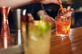 Koktejl. Barman připravuje koktejl v baru. Barman obloha staré staromódní koktejl s pomerančovou kůrou. Vysoké rozlišení