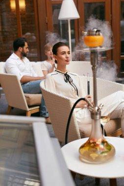 Woman Smoking Shisha In Hookah Bar. Beautiful Fashionable Girl Smoke Fruit Cup Hookah At Luxury Lounge Restaurant. High Resolution
