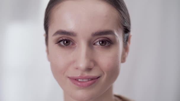 Péče o obličej Zenske. Usmívající se žena dotýká kůže na obličeji