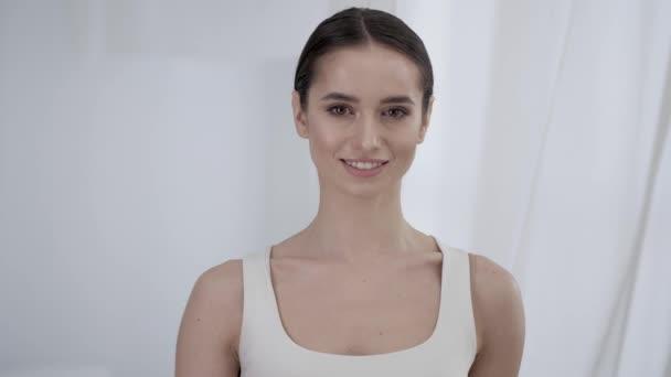 Ženská krása. Portrét krásné usmívající se dívka se dotýká kůže obličeje