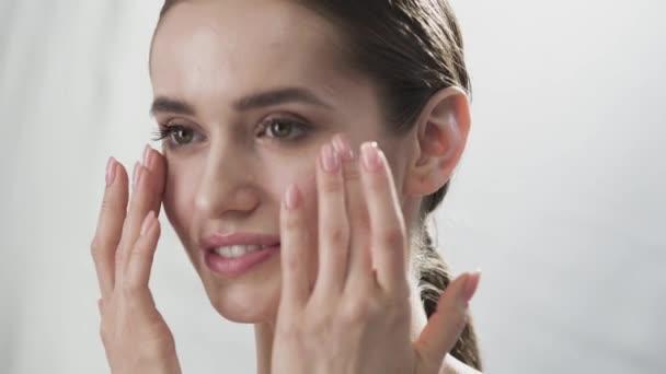 Péče o pleť obličeje. Žena dotýká kůže pod očima Closeup