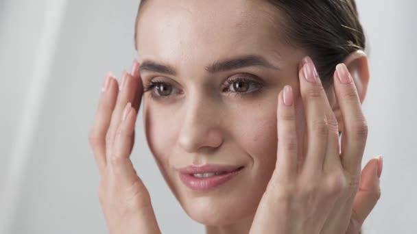 Cura della pelle del viso. Donna che tocca la pelle sotto gli occhi del primo piano