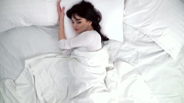 Žena spí v posteli s bílým ložním prádlem na domácí