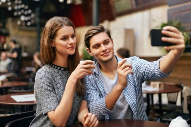 Couple Making Photo On Mobile Phone In Cafe. Woman And Man Having Date In Coffee House. High Resolution stock vector