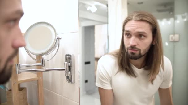 Bathroom. Man Looking In Mirror And Touching Face