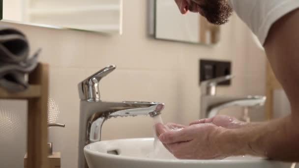 Reggel higiénia. Az ember arca, a fürdőszoba tiszta vízzel mosó