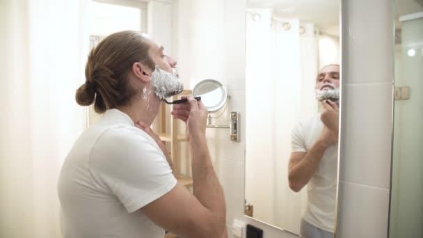 Muž holení vousů s břitvou v koupelně