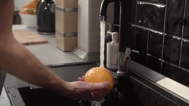 Washing Orange With Clean Water At Kitchen Tap Closeup